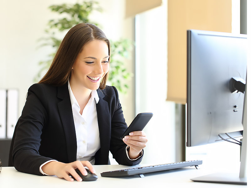 Happy Businesswoman Checking Smart Phone Text Sitting At Office